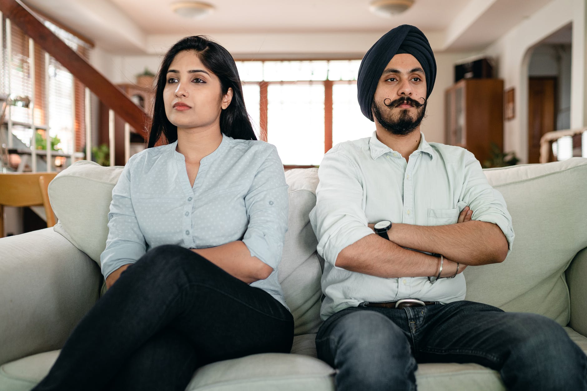 offended young indian couple sitting on sofa