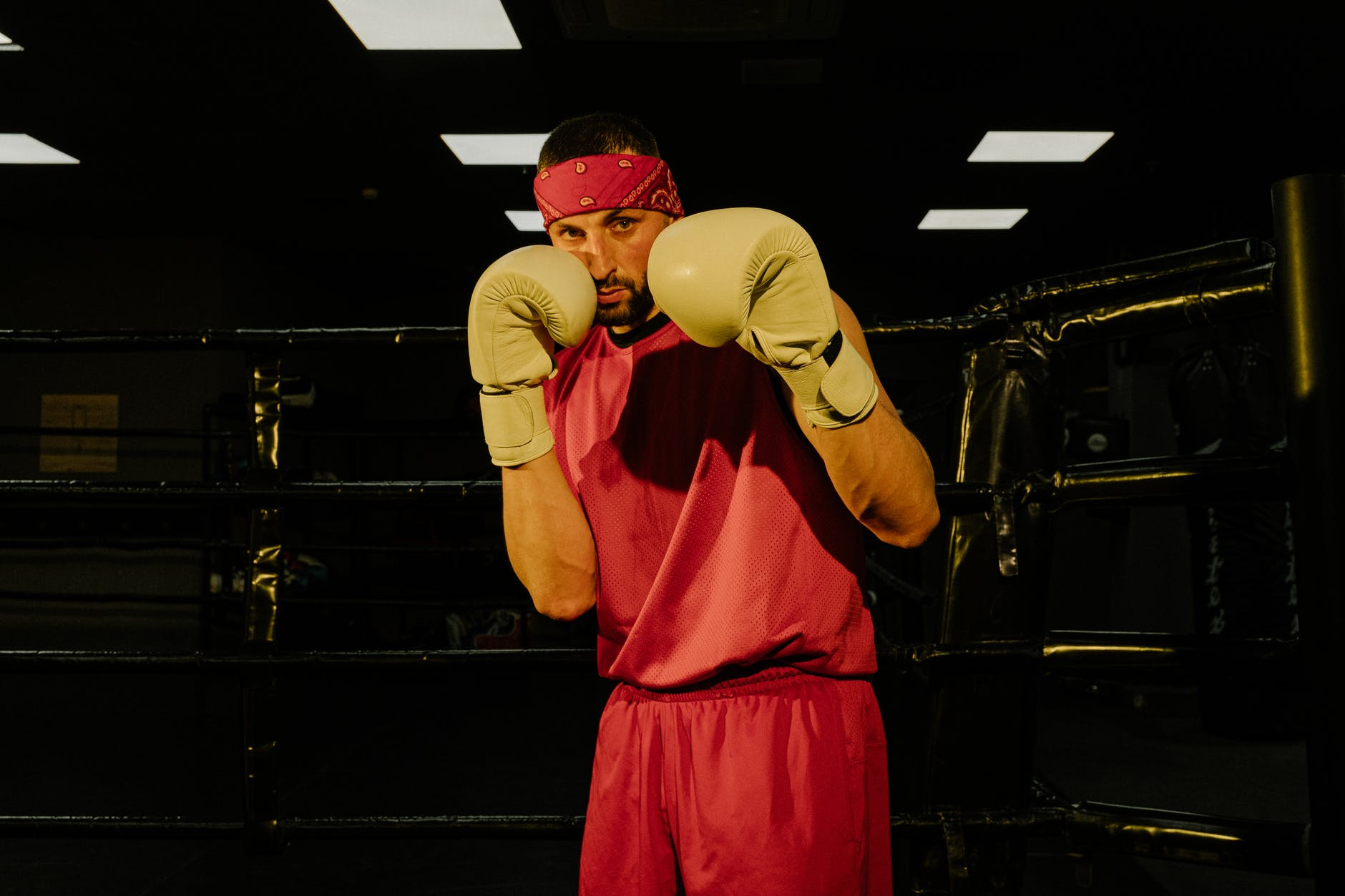 serious young male boxer training on ring