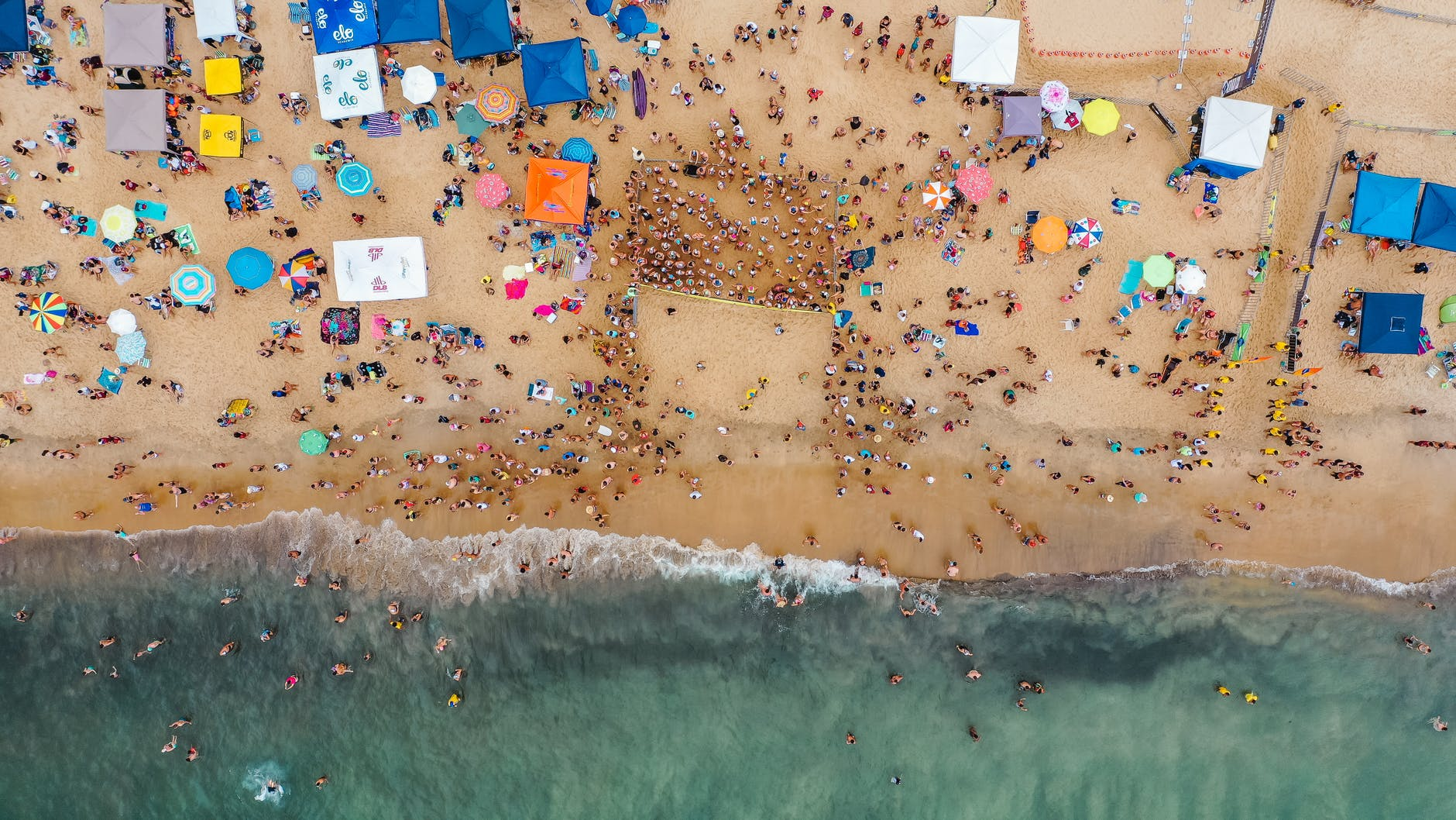 crowded ocean seashore from drone