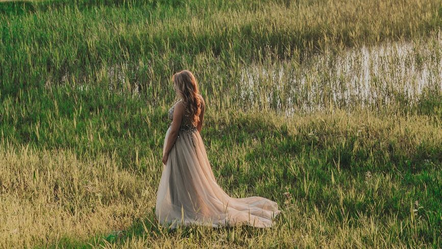 anonymous woman walking in field