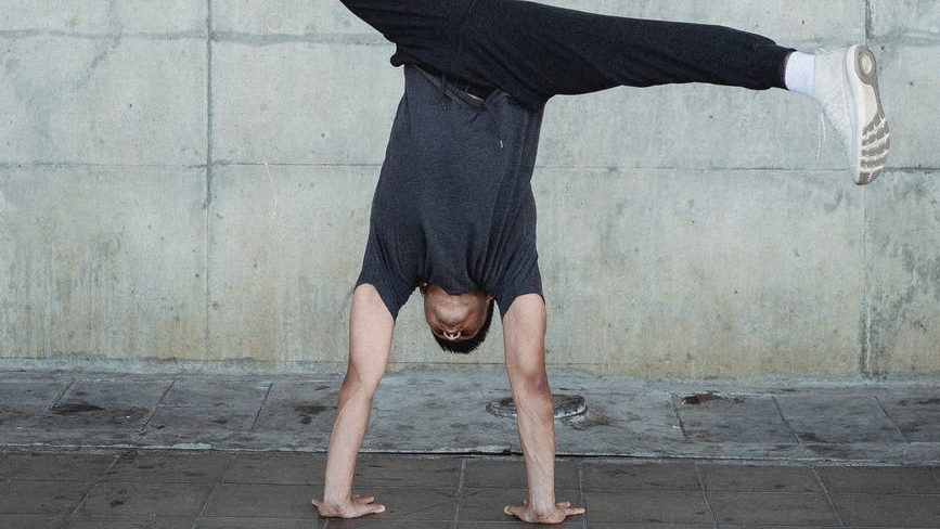 faceless man performing handstand and split in air