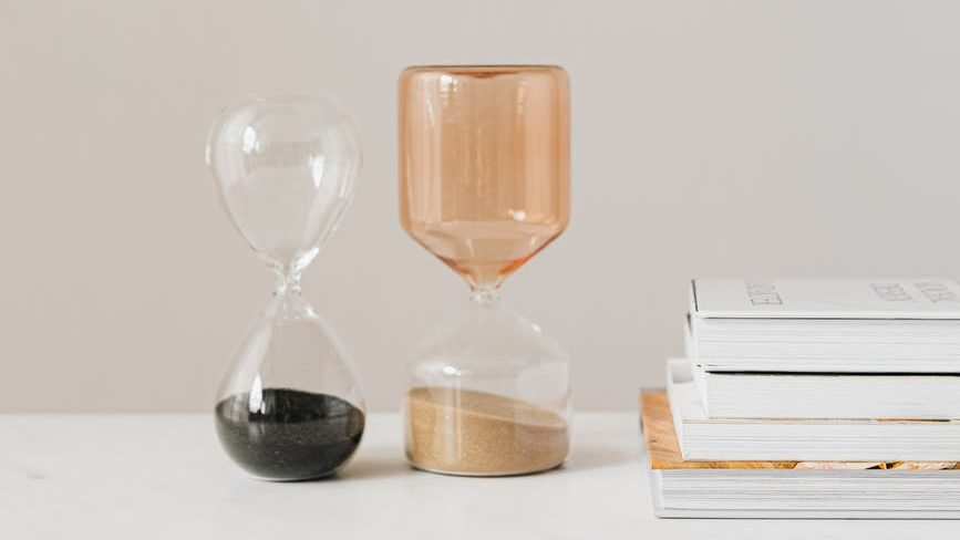 various decorative hourglasses on table near books