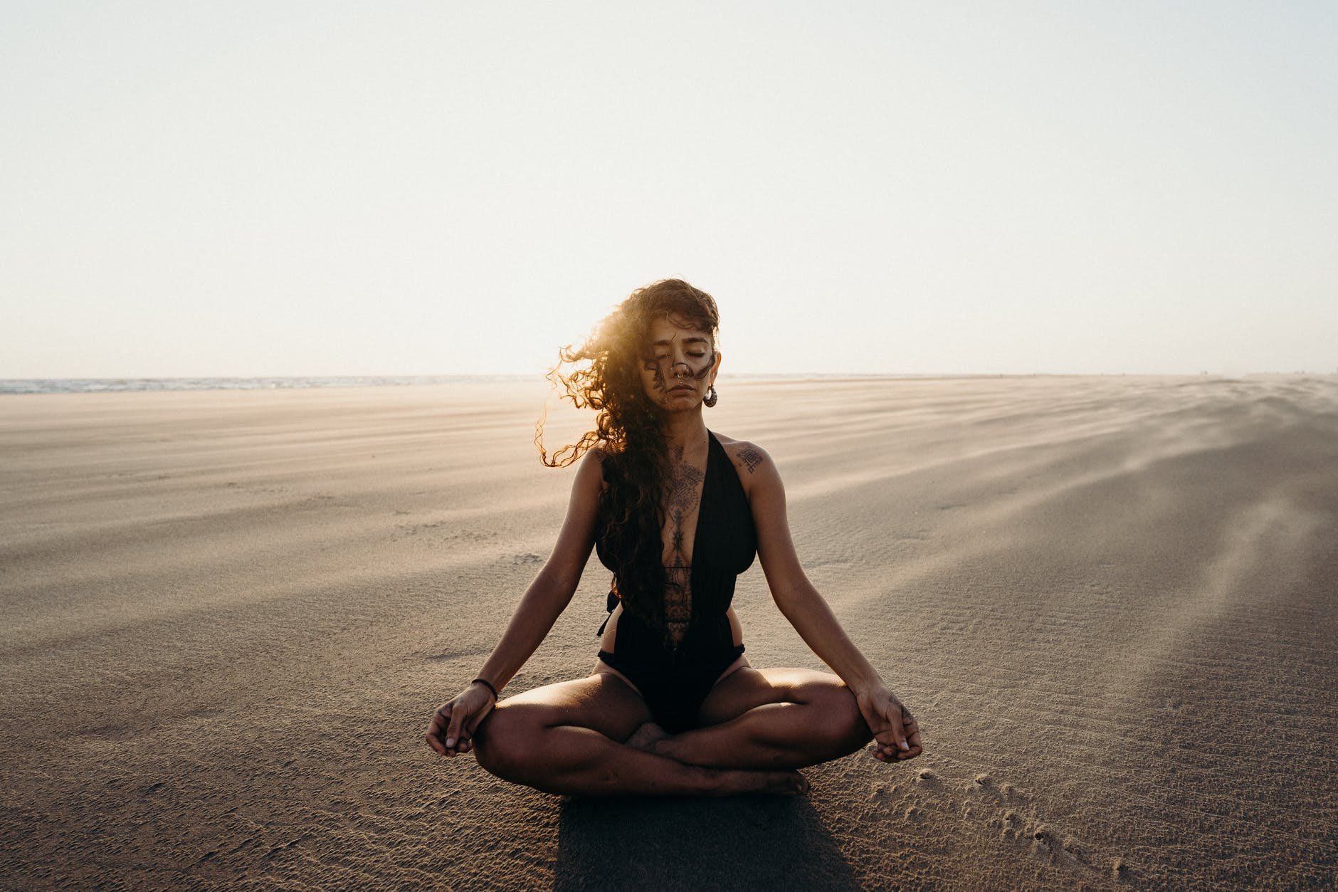 woman in black tank top and blue denim jeans sitting on brown sand