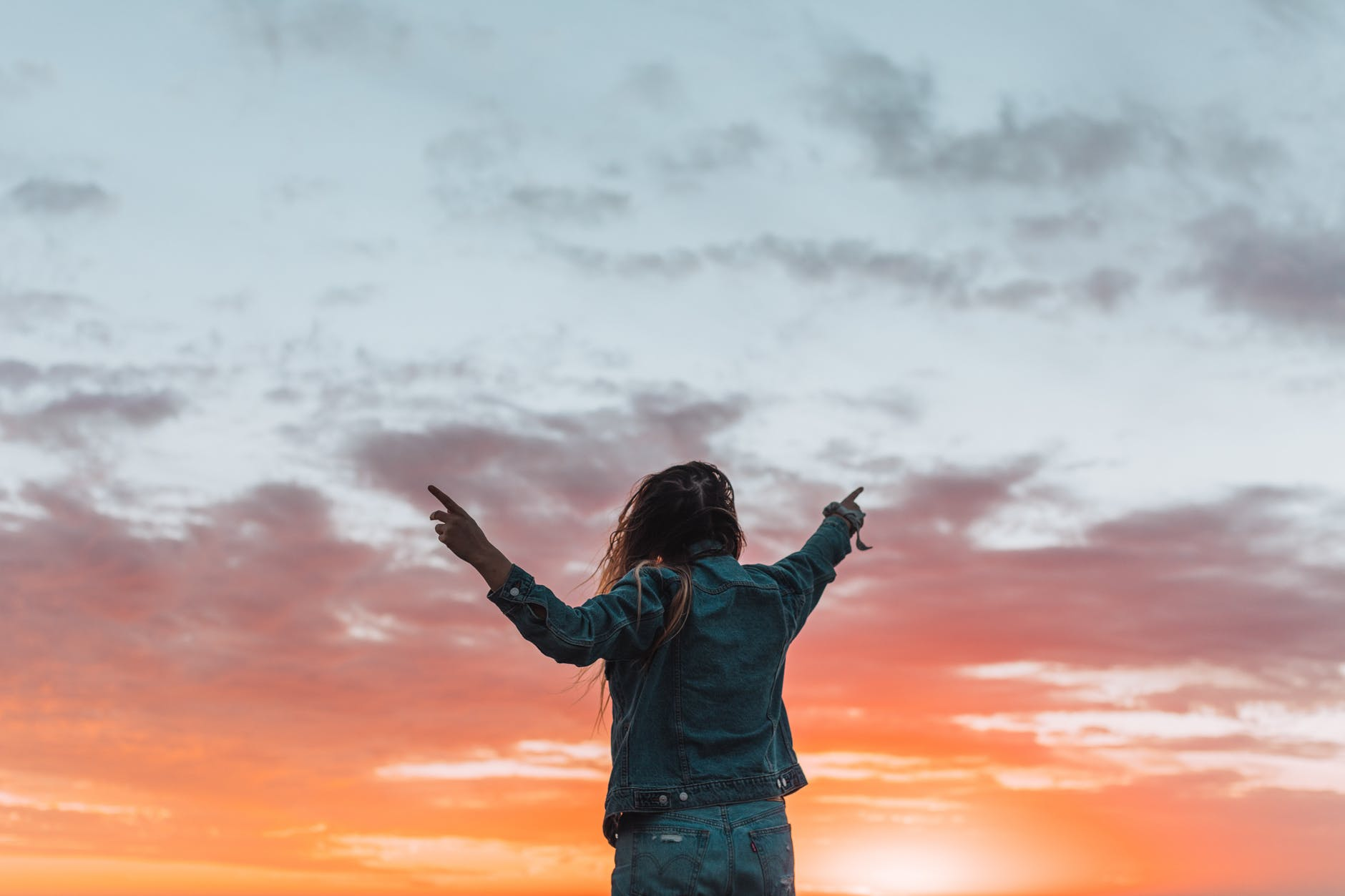 faceless woman pointing with fingers at bright sky in twilight