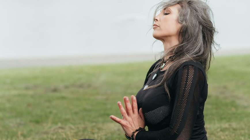 mindful woman meditating with praying hands in lotus pose
