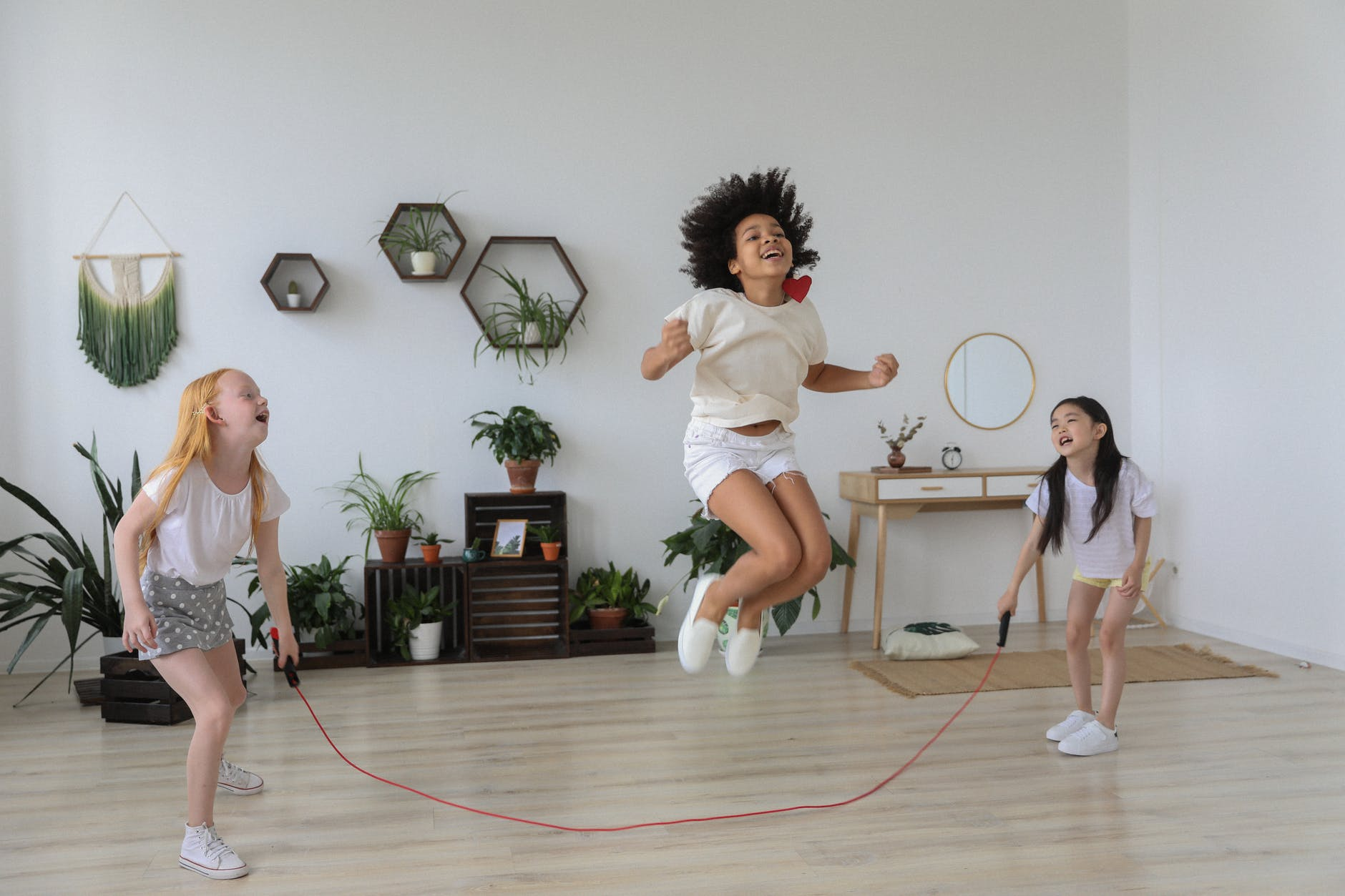 black girl jumping over rope while playing with friends