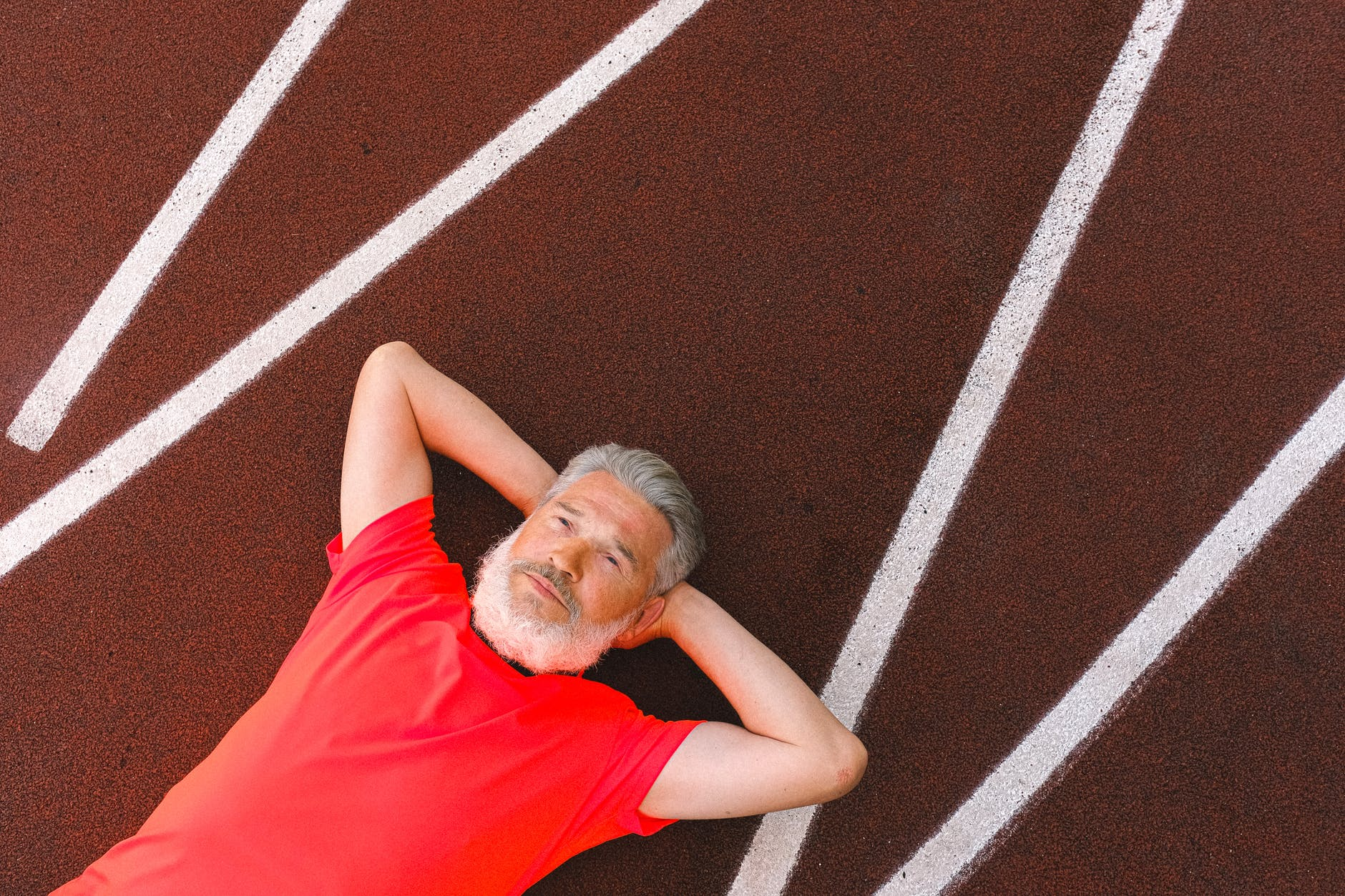 senior man with beard resting peacefully on racetrack