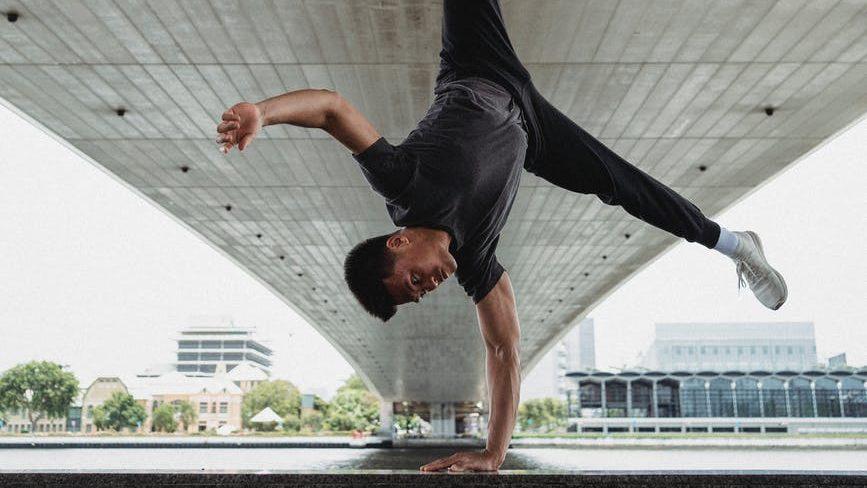 sportsman doing handstand under bridge in city