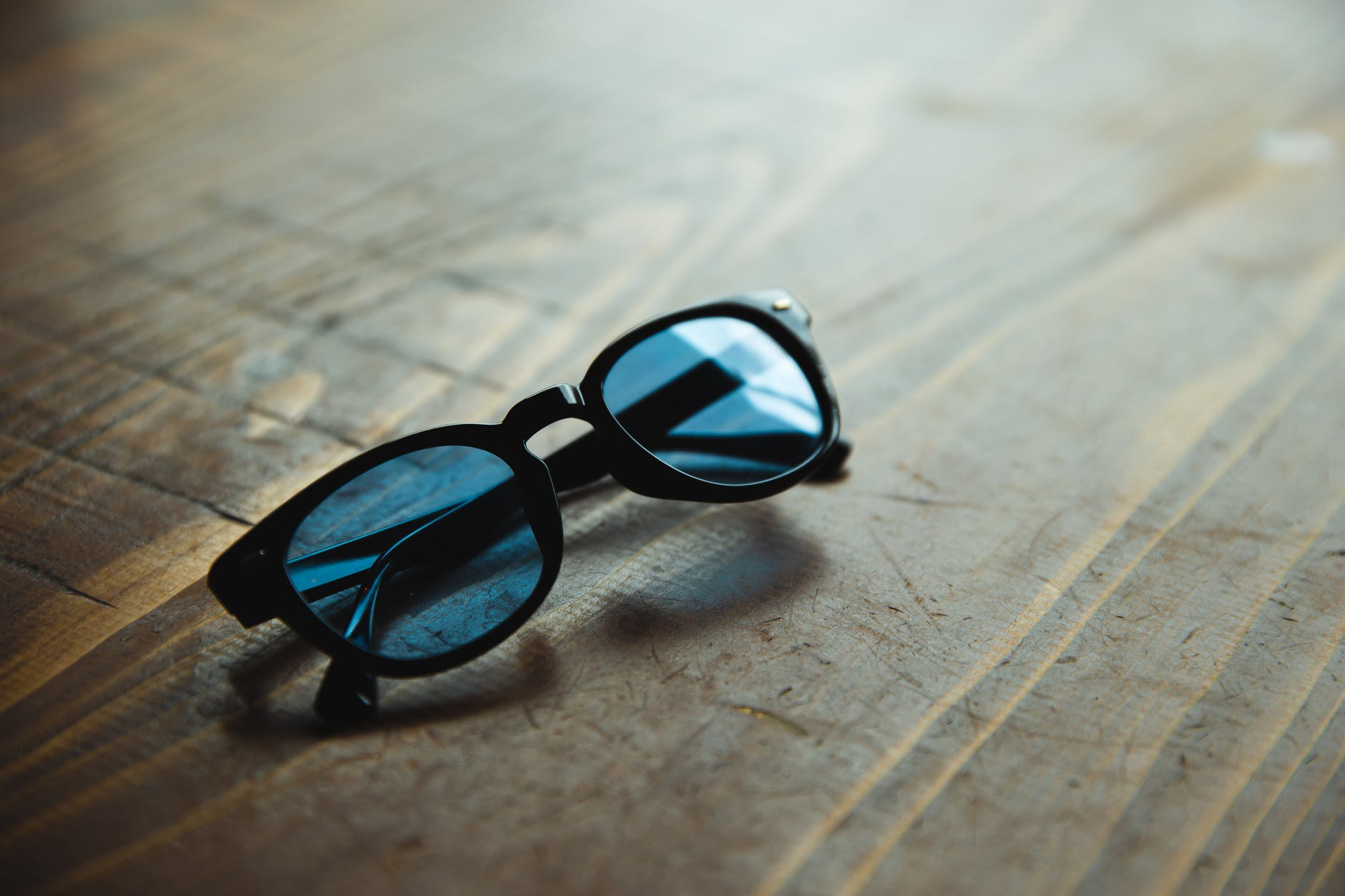 trendy sunglasses placed on wooden table