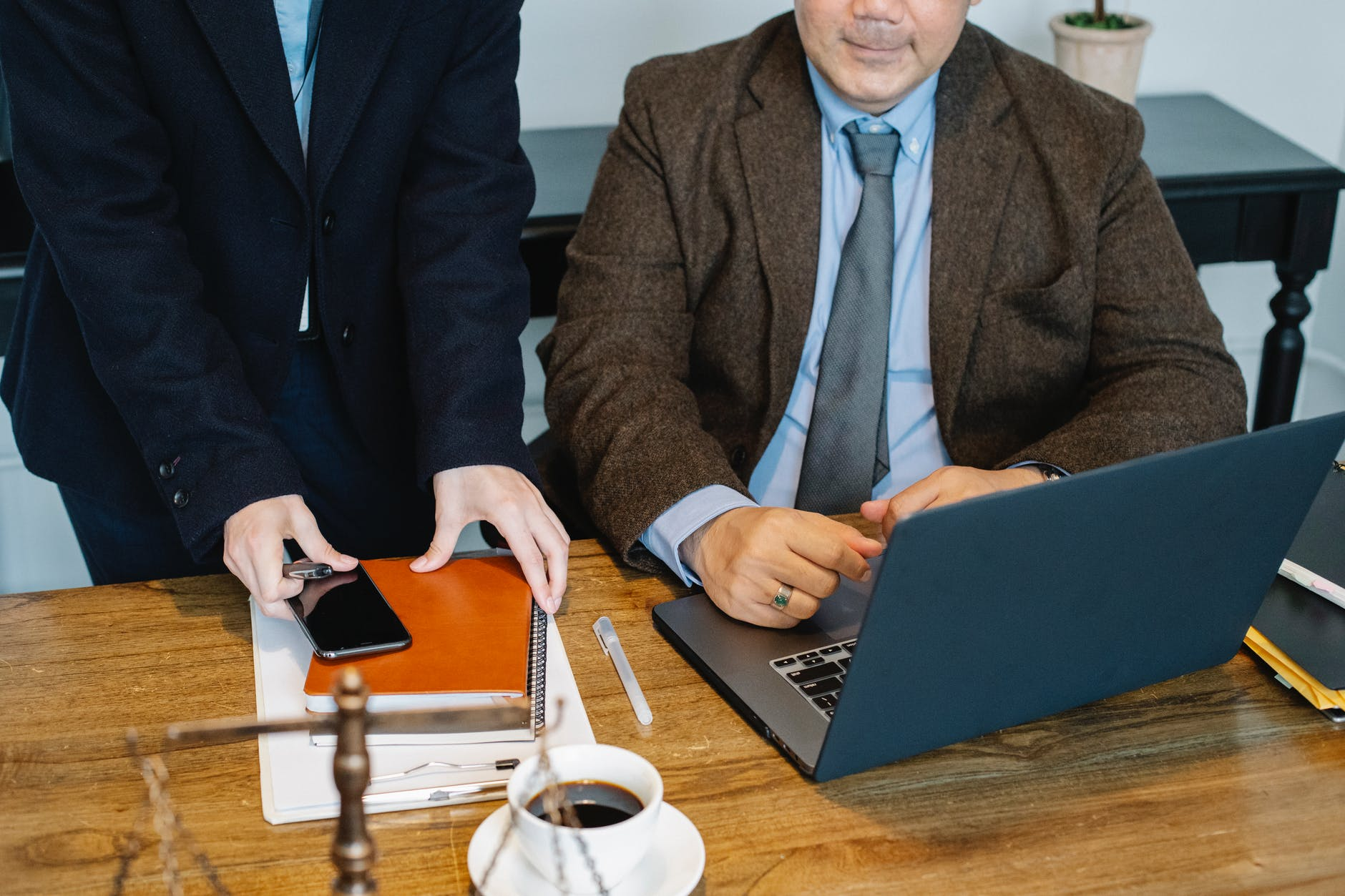 crop colleagues gathering at table with laptop in office