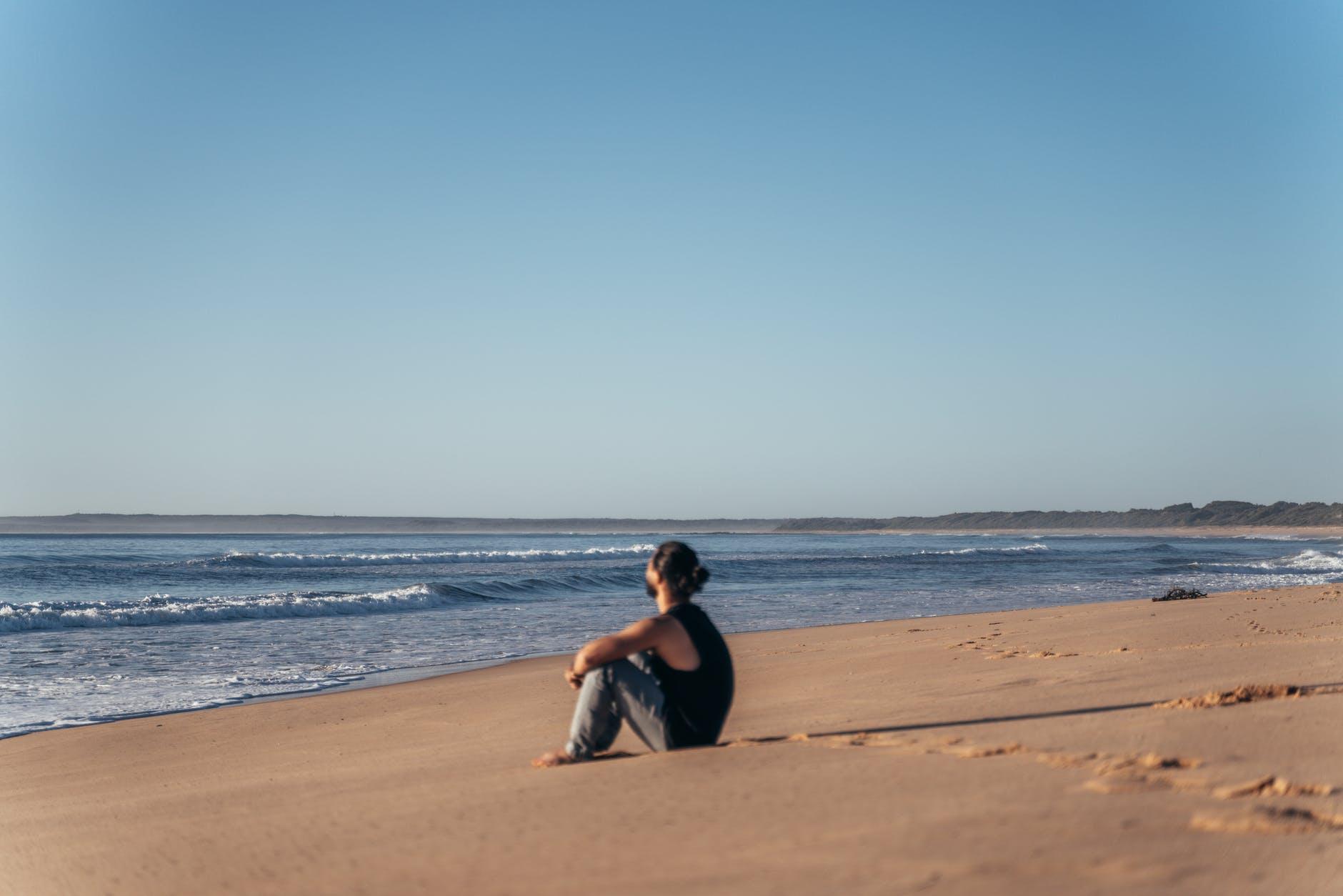 unrecognizable man resting on sandy calm beach
