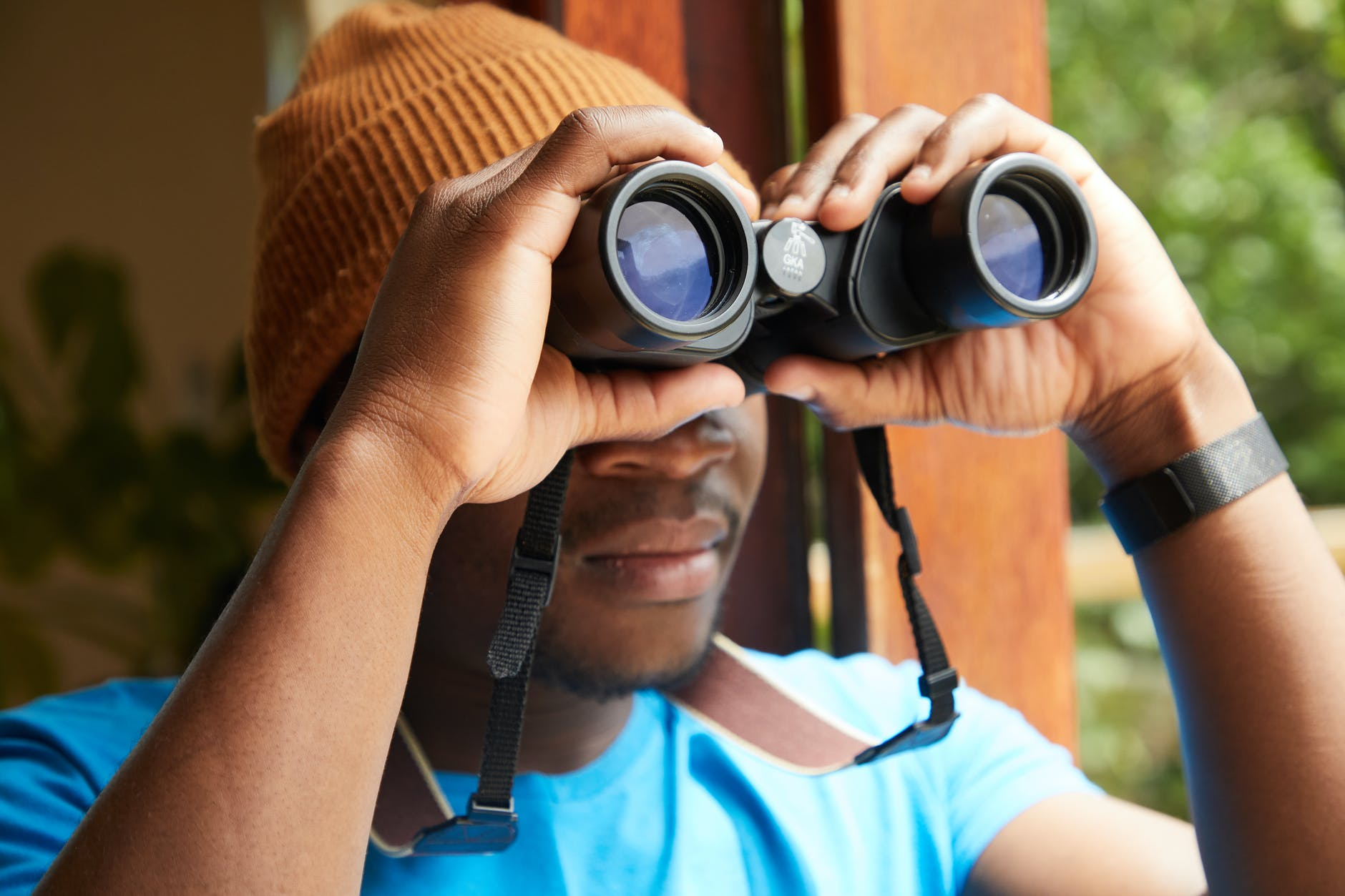 black man with binoculars near window