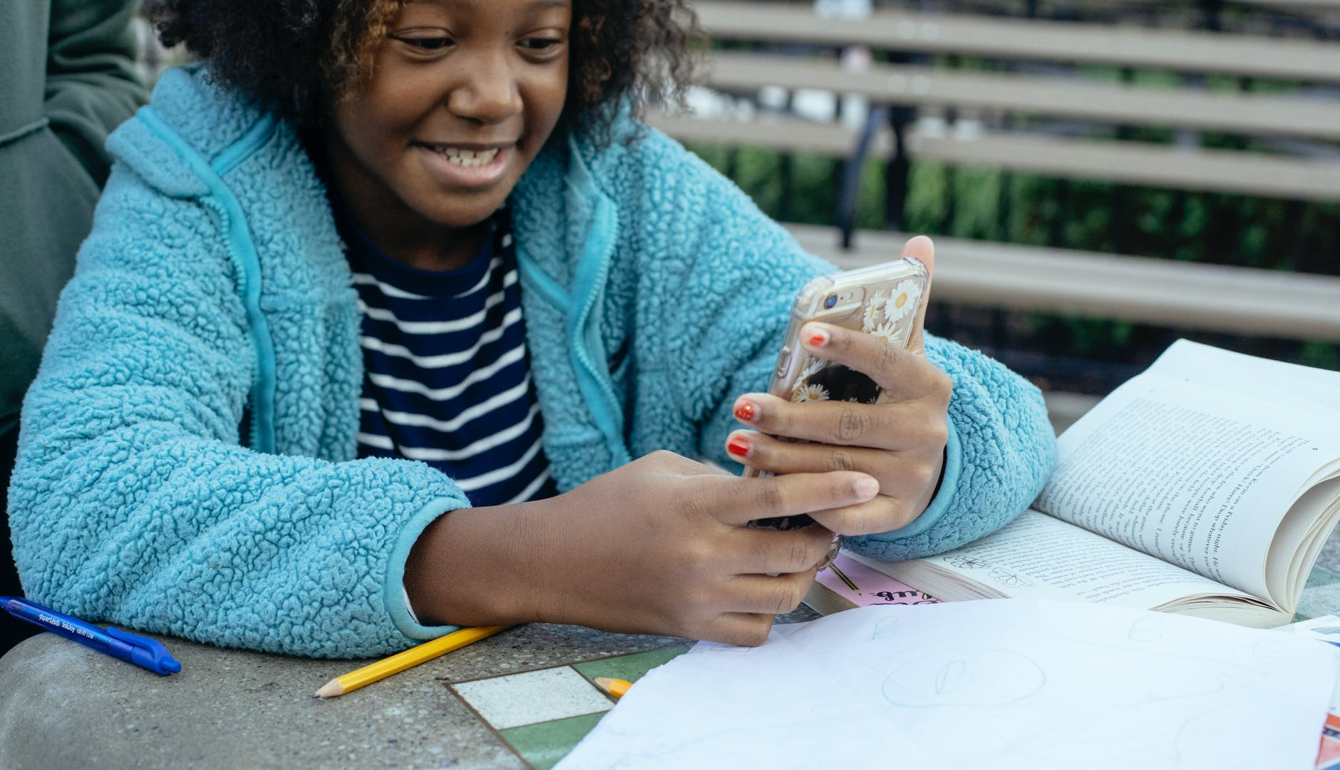 black girl browsing smartphone during homework