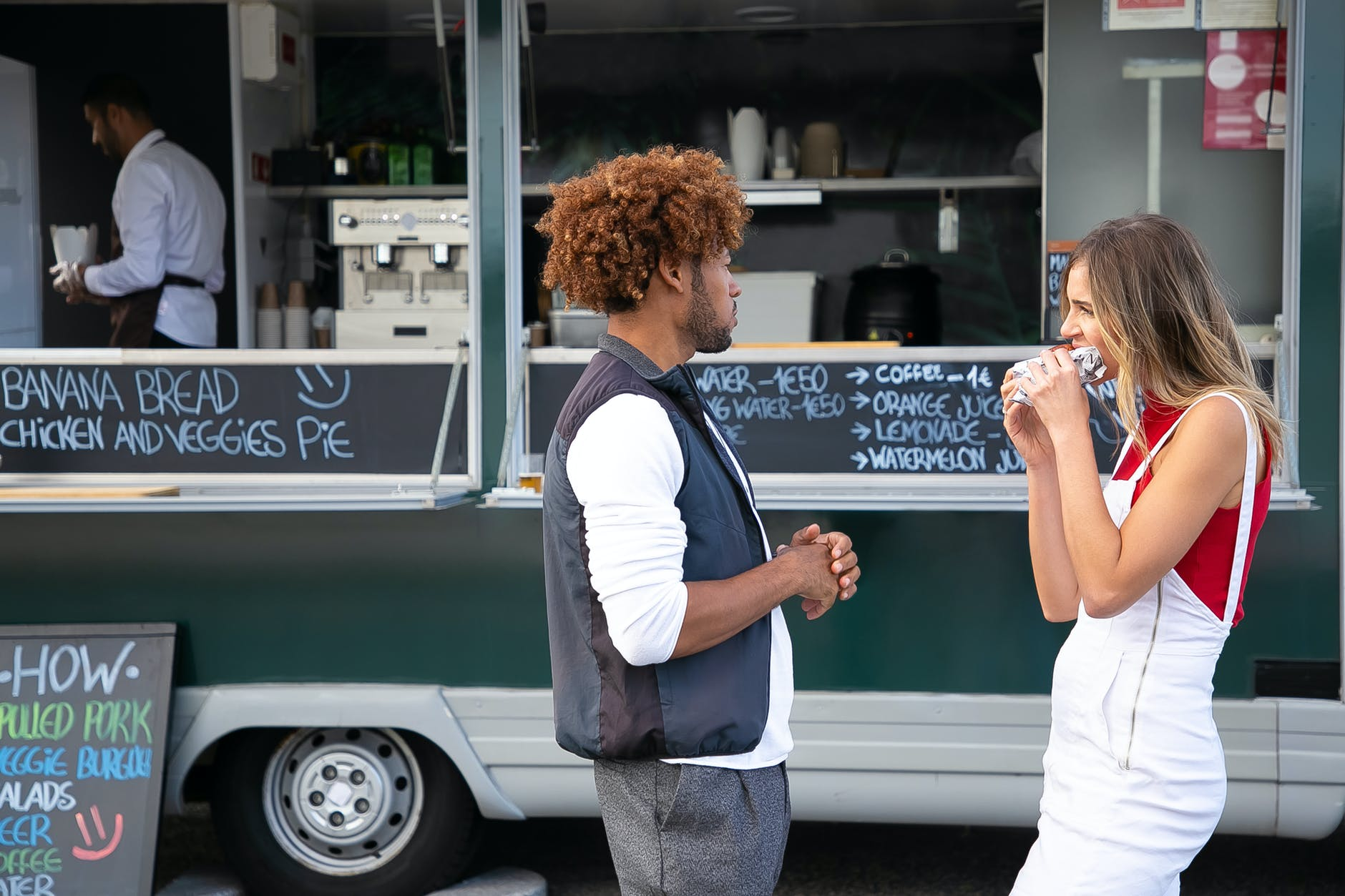 young diverse couple eating takeaway sandwich while standing near food truck