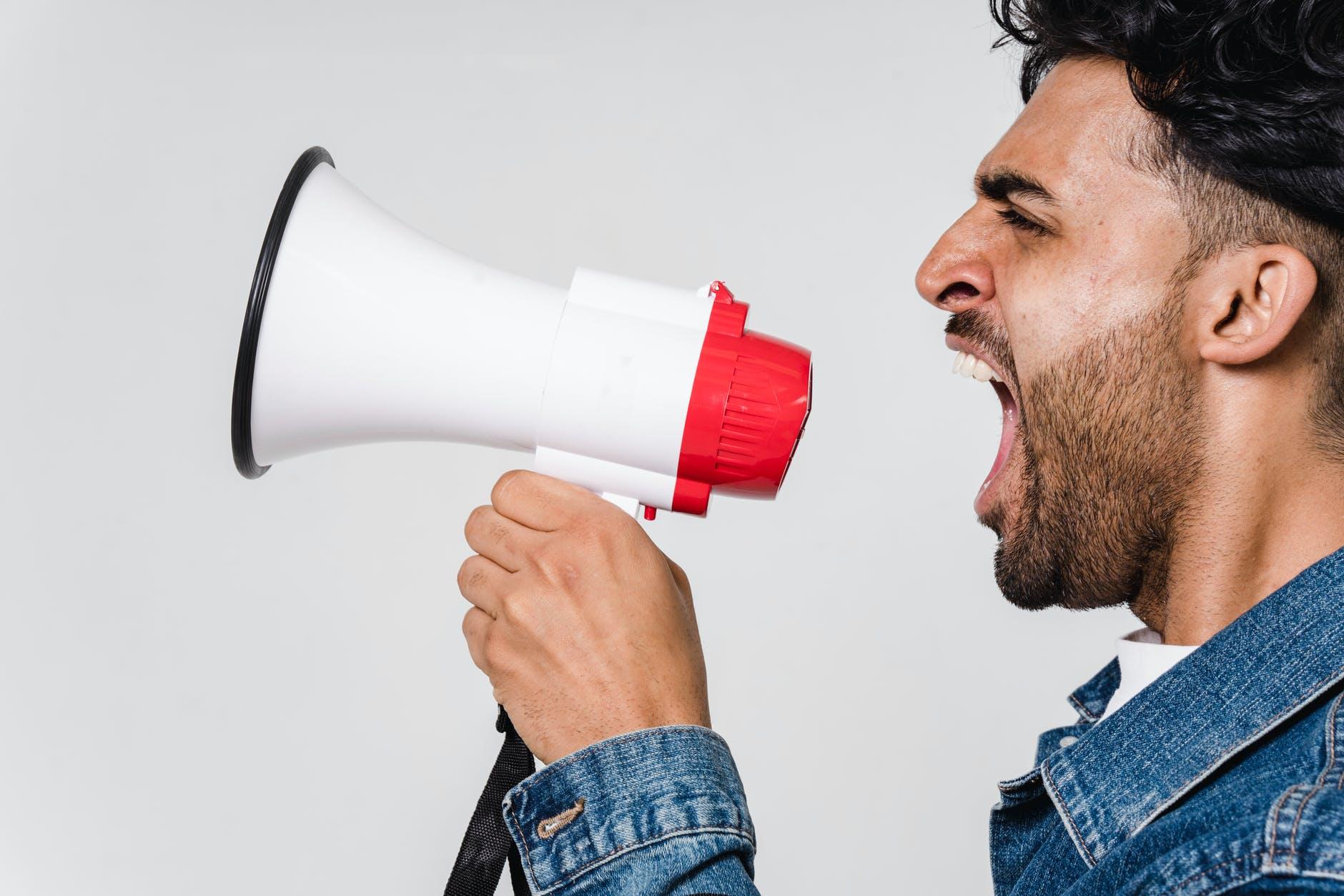 man in blue denim jacket holding a megaphone