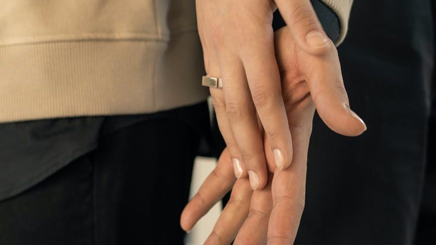 person in beige long sleeve shirt and black pants holding hands