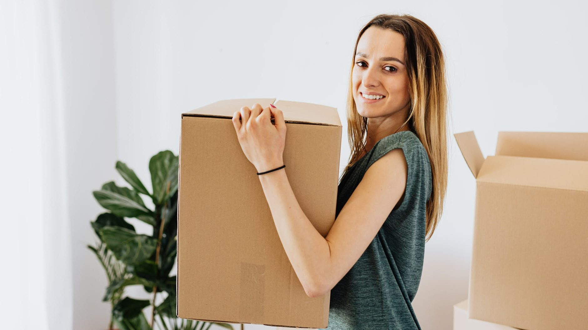 cheerful woman carrying packed carton box