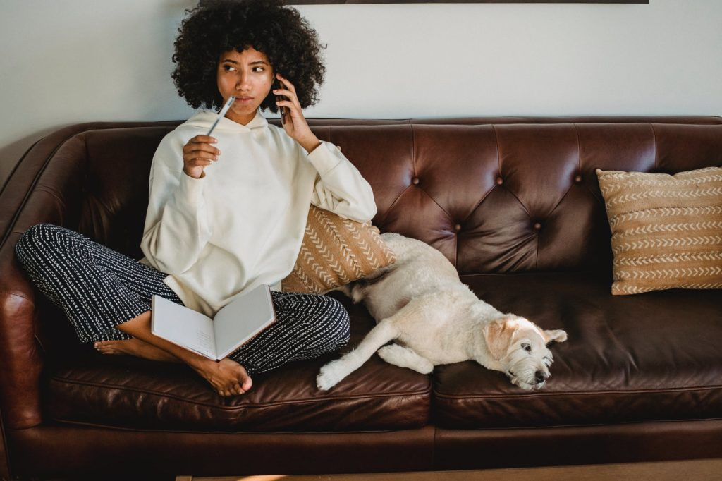 thoughtful black woman with notebook and dog on leather sofa