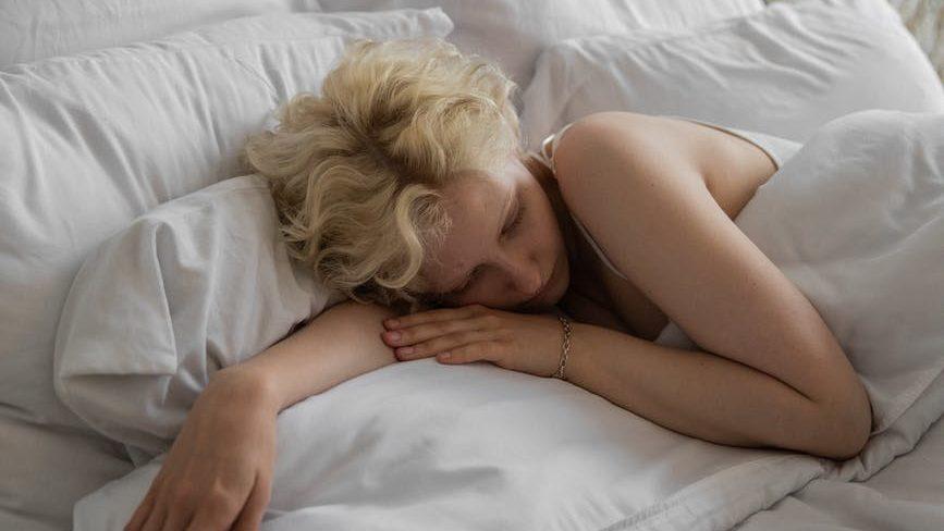 sleepy woman lying on bed with alarm on smartphone