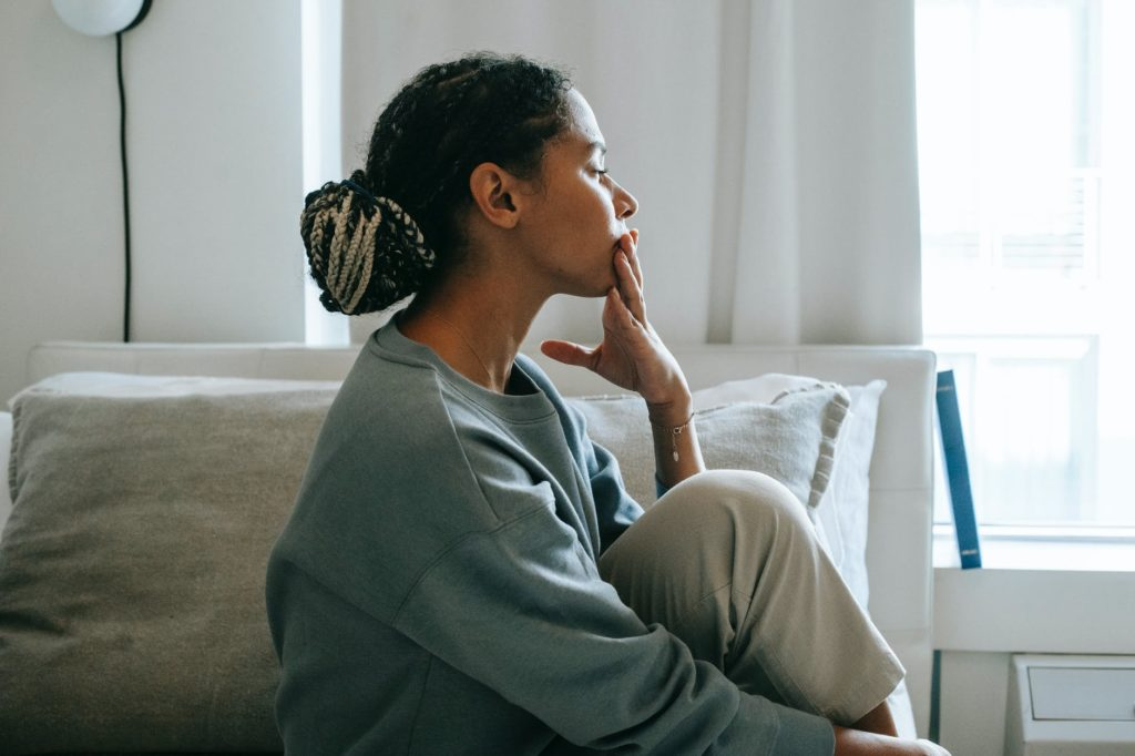 black female sitting on bed in room