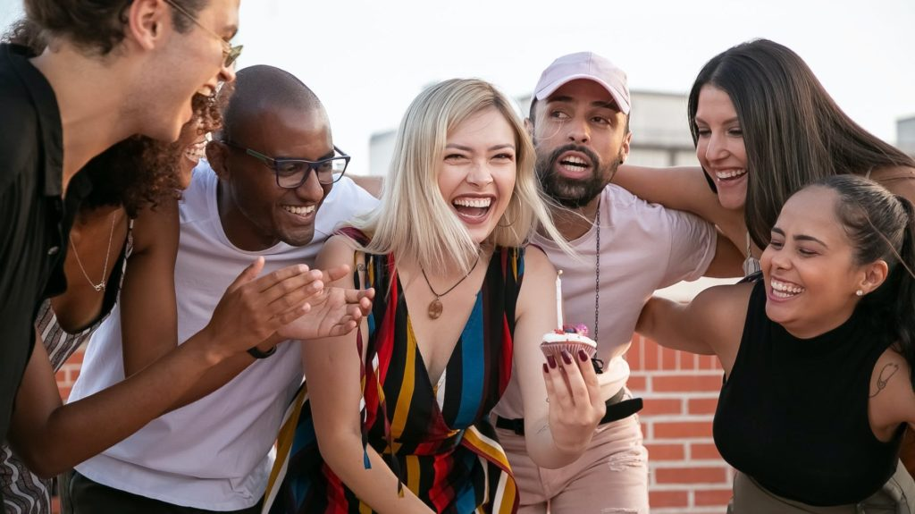 excited young diverse friends celebrating birthday of cheerful woman on terrace